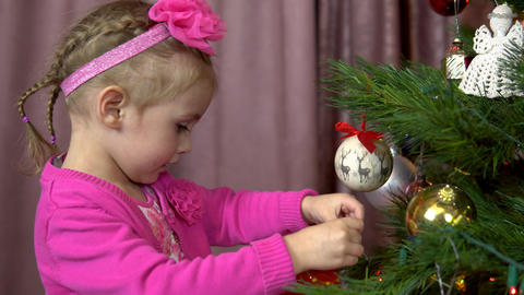 Little girl decorates a Christmas tree. A child hangs a ball on a Christmas tree Live Action