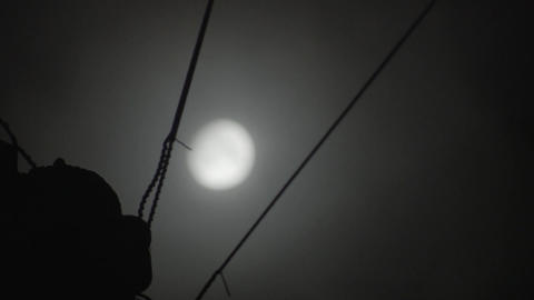 Cloudy winter moon timelapse across a telephone wire Live Action