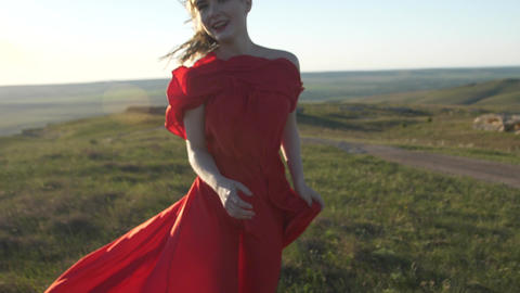 Blurred image of a woman in a red dress running across the field and laughing GIF