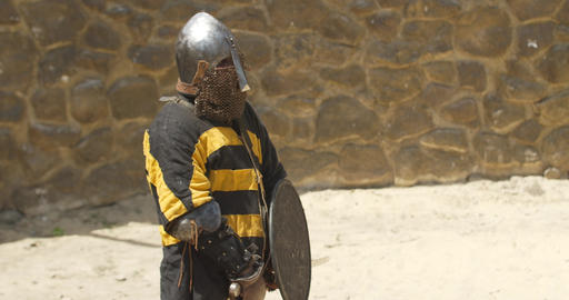 Warrior in armor with sword in hand is standing in the middle of arena Live Action