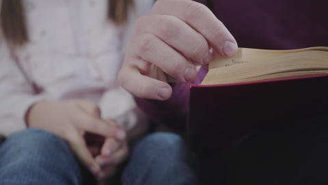 Close-up of adult male Caucasian hands turning pages. Little girl's hand showing Live Action