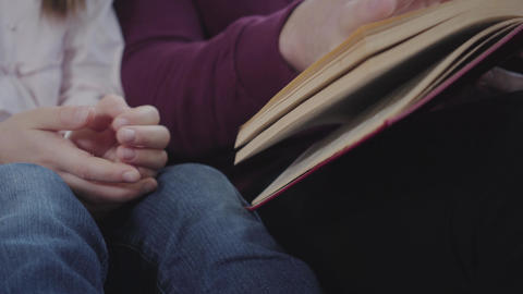 Adult Caucasian man and teenage girl sitting with book. Male hand turning pages Live Action