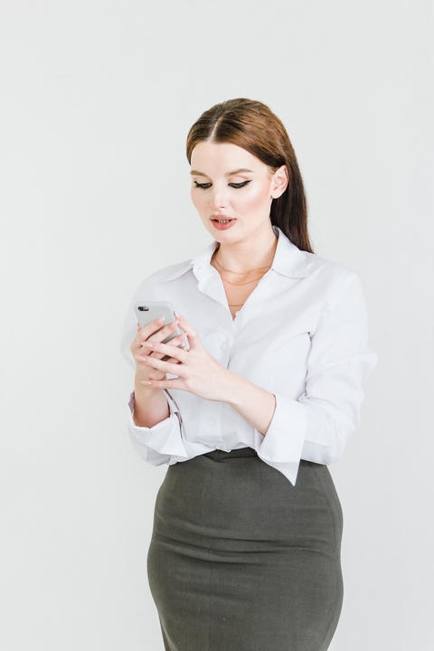 A business woman in a skirt and blouse with a mobile phone in her hands performs Photo