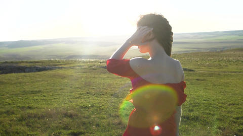 A young woman in a red dress stands in the background of a light filled field of Live Action