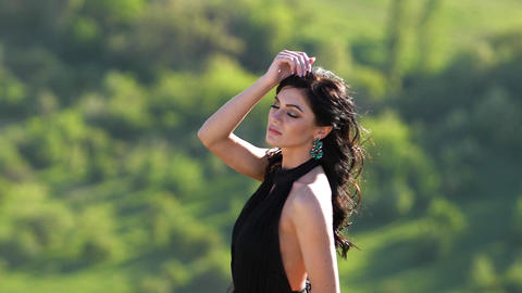 Young woman with beautiful eyes in black dress posing in background of green GIF