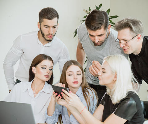 A company of young people having a meeting and watching information on a tablet Photo
