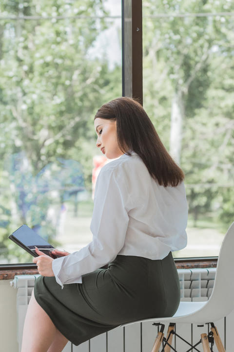Young beautiful woman in a business suit is sitting by the office window In her Photo