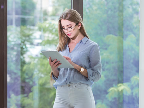 Beautiful young female employee with a tablet computer in her hands working in a Photo