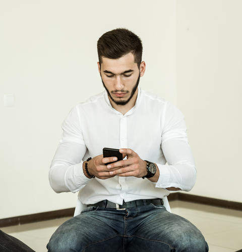 A young man with a beard in a white shirt works with a smartphone while sitting Photo