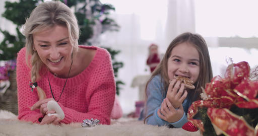 Positive Caucasian mother and daughter laughing out loud as eating cookies at Live Action