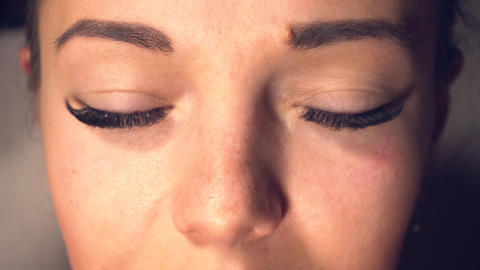 Woman with long eyelashes open her eyes and looking in camera Live Action