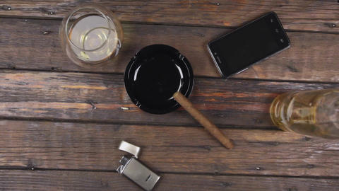 Top view of a cigar on an ashtray, a glass of alcohol and lighter next to a Live Action