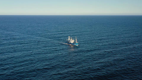 Bird's eye view of a fishing boat sailing in the Atlantic Ocean Live Action
