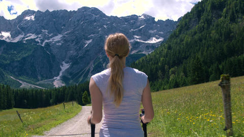 Mid shot - Walking behind young woman on a hike to the mountains with poles Footage