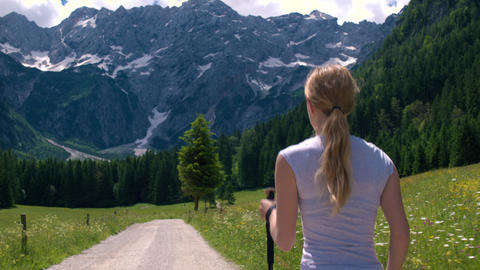 Walking behind young woman on a hike to the mountains with poles in spring Footage