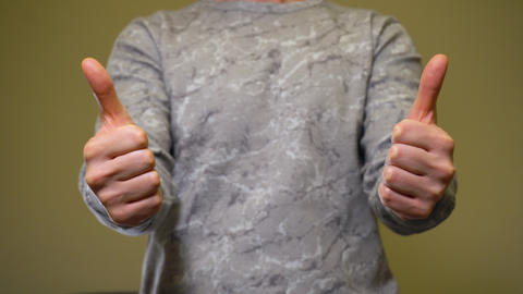 Man show thumbs up by two hands. Approval gesture Live Action