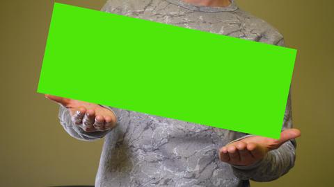Man raises empty green screen chromakey banner over hands Live Action