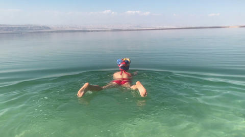 Funnny woman trying to swim in a dead sea, floationg ass, natural jordan, clumsy Live Action