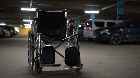 An empty wheelchair stands in the middle of a car park. Wheelchair is standing Live Action