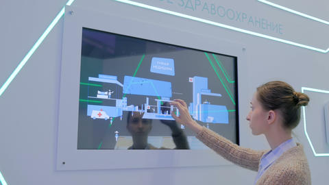 Woman using multimedia touchscreen display of interactive kiosk Live Action