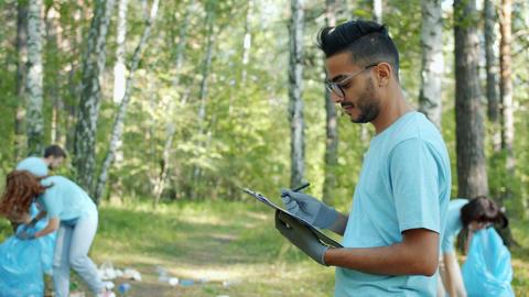 Portrait of Arabian man volunteer doing paperwork during park clean-up in summer Live Action