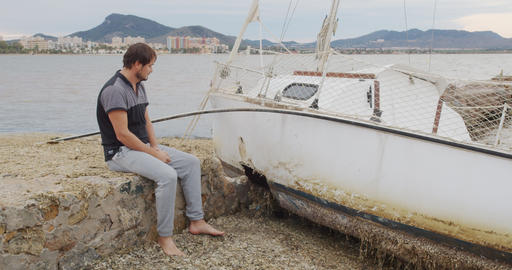 The man sits in despair near his yacht broken after a storm Live Action