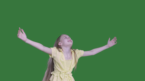 Happy girl teenager with raised hands twisting on green background. Smiling girl Live Action