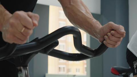 Hands of fitness man holding handle indoor bike on cycling class. Sweaty man man Live Action