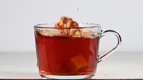 Throwing brown sugar cubes in cup of black tea Live Action