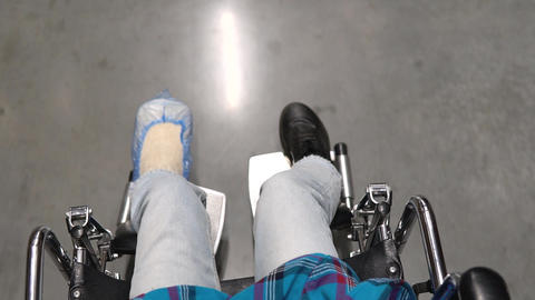 Top view of a young woman riding a wheelchair. Woman with a broken leg Live Action