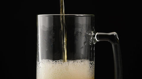 Close up pouring lager beer in glass over black Live Action