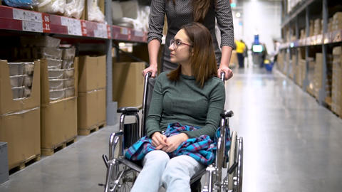 A young woman is sitting in a wheelchair. Female assistant drives a woman in a Live Action