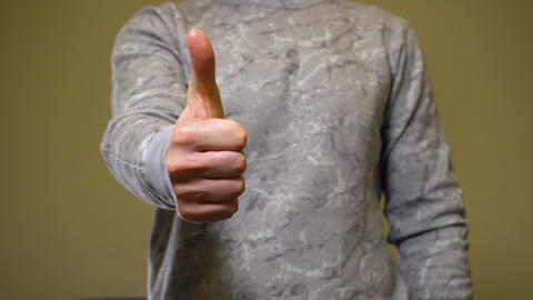 Man in gray show gesture thumbs up Live Action