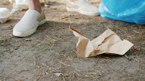Close-up of person's hand collecting trash in park participating in clean-up Live Action