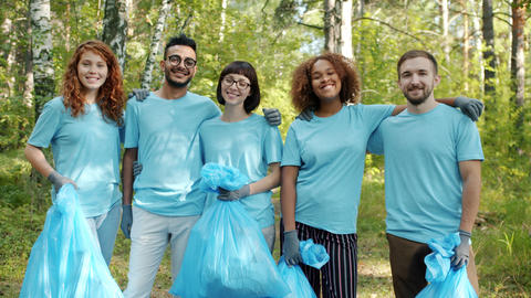Cheerful youth volunteers with garbage bags standing in forest hugging smiling Live Action