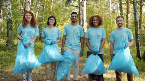 Portrait of young people volunteers in forest holding garbage bags smiling Live Action