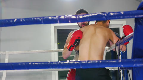 Boxing in the gym - two athletic men having a training fight on the boxing ring Live Action