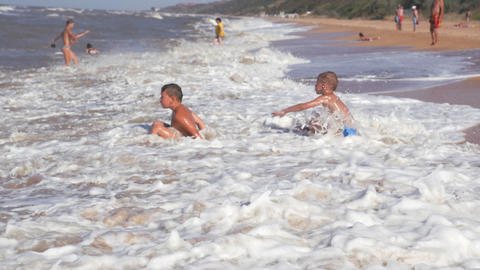 Beach summer vacation. Children in the raging waves Live Action