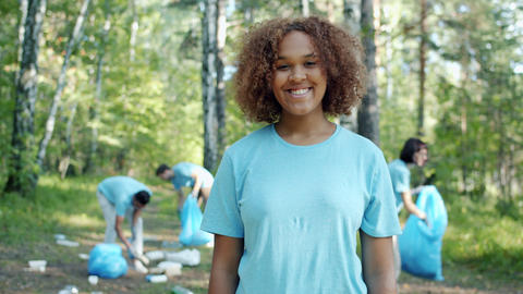 Portrait of happy Afro-American girl in volunteer uniform in polluted forest Live Action