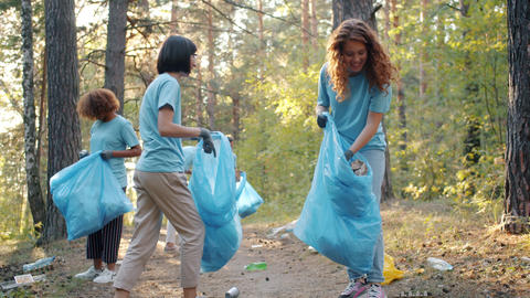 Cheerful youth cleaning forest from garbage in summer doing voluntary work Live Action