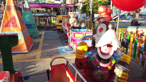 Young Children Ride On A Colorful Train Carousel GIF