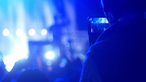 People at the concert in the club - a man recording the concert on his phone Live Action