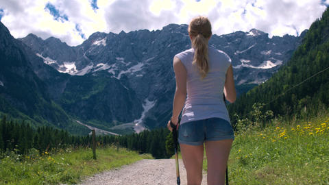 Low angle view - Behind young woman walking to the mountains with hiking poles Footage