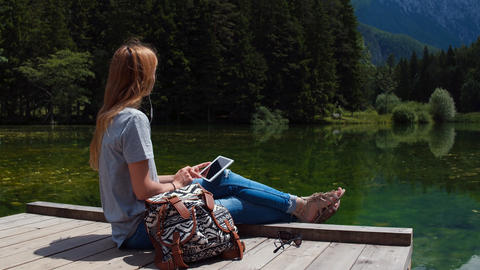 Young woman of caucasian ethnicity sitting on pier at the lake with tablet Footage