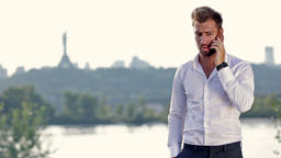 Young businessman talking on mobile phone outdoors Footage