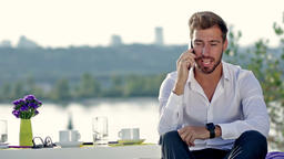 Handsome man talking on the phone outdoors Live Action
