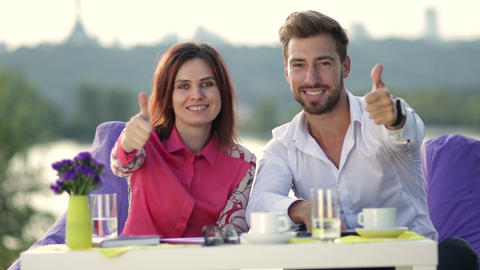 Smiling business people giving thumbs up sign Live Action