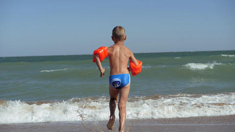 Boy runs into the sea. Waves wash over the beach. Child in armbands on vacation Live Action