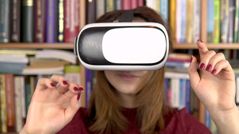 Young woman in VR glasses in the library. A woman with a VR helmet on her head Live Action