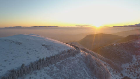 Aerial view of sunset sunrays shining on winding mountain road and snow covered Live Action